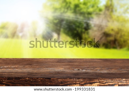 brown wooden desk and green space of summer landscape