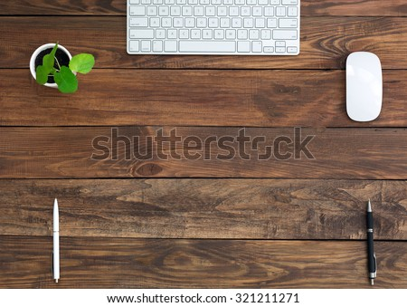 Brown Wooden Desk with Stationery and Electronics\ Natural Wood Background Small Green Plant Computer Mouse and Keyboard Black and White Pens Top View