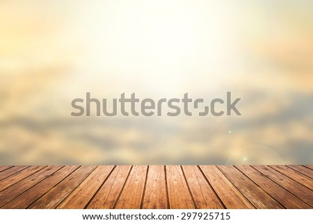 Brown wooden floor with abstract blurred background in sunset sky tone color and sunlight on top. use for backdrop or web design