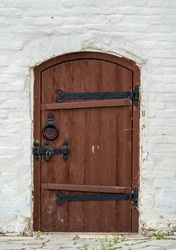 Brown wooden medieval church door on white old monastery building