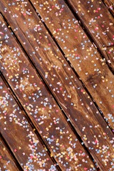 Brown wooden planks strewn with multicolored confetti in the shape of the moon and stars.