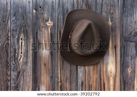 brown wool felt cowboy hat with leather headband hanging on weathered wooden wall of old barn