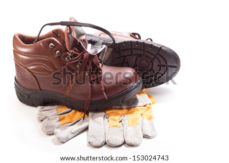 Brown work boots, gloves and goggles for safe operation on a white background
