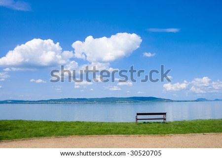 Brown wrought iron bench at the beach of Lake Balaton with nice cloudscape.