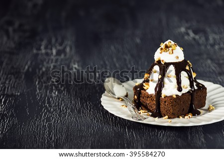 Brownie Sundae with a Scoop of Vanilla Ice Cream, Chocolate Sauce, Whipped Cream, and Nuts with Copy Space