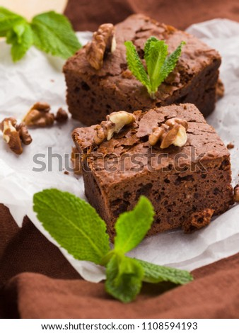 Brownie sweet chocolate dessert with walnuts and meant leaves on white paper with copy space on pastel beige background - beautiful banner with delicious brown cocoa baked pastry.