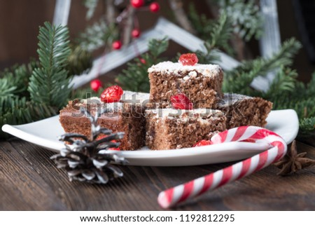 Brownies for Christmas and winter holidays. Homemade chocolate fudge brownies with decorations on rustic wooden table.