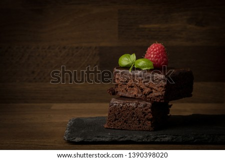 Brownies, stacked brownies on plate with raspberry and mint isolated on wooden background, copy space #1390398020