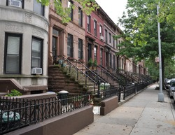 Brownstone Homes along residential Neighborhood sidewalk in Brooklyn New York on overcast sky day