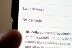 Brucellosis News on the phone.Mobile phone in hands. selective focus and chromatic aberration effects.
