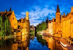 Bruges, Belgium. Image with Rozenhoedkaai in Brugge, Dijver river canal twilight and Belfort (Belfry) tower.