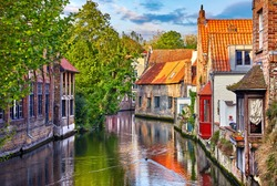 Bruges, Belgium. Medieval ancient houses made of old bricks at water channel with boats in old town. Summer sunset with sunshine and green trees. Picturesque landscape.