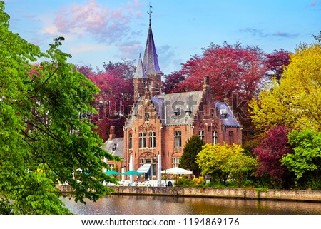 Bruges (Brugge), Belgium. Minnewater lake of love in picturesque park. Traditional ancient medieval castle with tower on bank among trees with red, pink, yellow and green crowns. Picturesque.