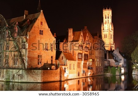 Bruges by night (Belgium). Old houses near the waterfront with belfry tower at the background.