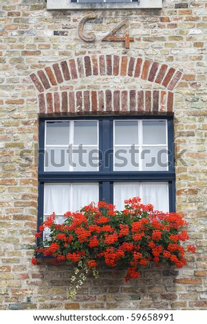 Brugge, Belgium. Old building with red flowers in windows
