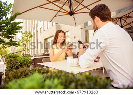 Brunch in nice outdoors summer terrace with modern interior and green nice plants, teens are browsing on their phones, smiling #679913260