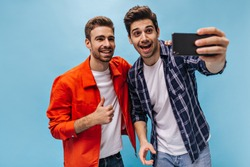 Brunet bearded man in jeans and checkered shirt takes selfie with friend. Cool guy in orange jacket shows thumb up on blue background.