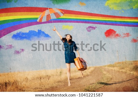 Photo of Brunet girl fly away with umbrella and suitcase at countryside. Image made in old color style