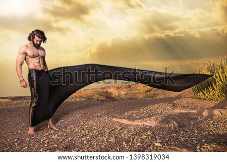 Brunette Asian Young handsome muscled fit male model man posing outdoor showing his abdominal muscles cloth flying in air fantasy style - Image
