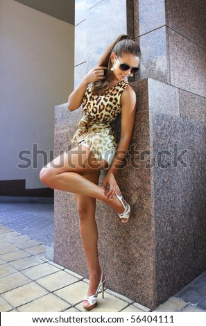 brunette beautiful woman stands near wall of building