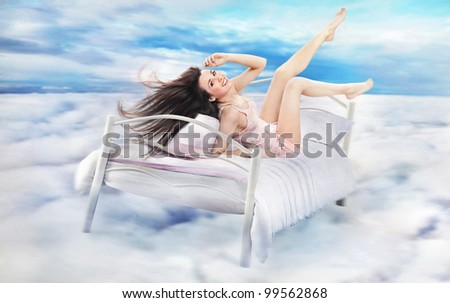 Brunette beauty lying on a bed in clouds
