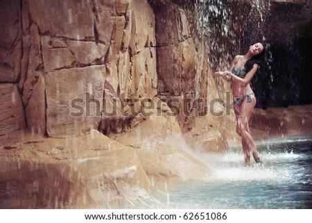 Brunette beauty taking bath in a waterfall