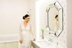 Brunette bride posing in bathroom