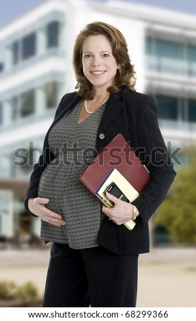 brunette business woman, mid 40's, holding note books and phone, building in background