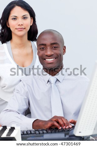 Brunette businesswoman and her colleague working at a computer in the office