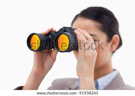 Brunette businesswoman looking through binoculars against a white background