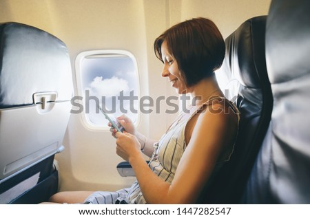 Brunette caucasian woman siting inside aircraft like passenger and taking a picture from smart phone