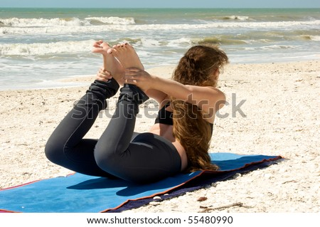 Brunette caucasian woman with long hair on beach doing Bow Yoga Pose, Dhanurasa,  on mat in the florida in the gulf of mexico