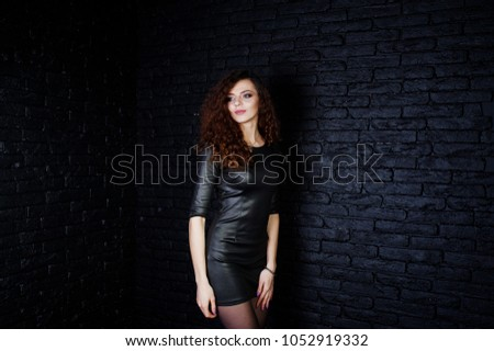 Brunette curly haired long legs girl in black leather dress posed at studio against dark brick wall. #1052919332