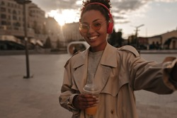 Brunette dark-skinned woman listening to music in red headphones and taking selfie outside. Happy lady in trench coat holds orange juice glass.