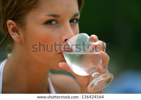 Brunette drinking glass of water outdoors
