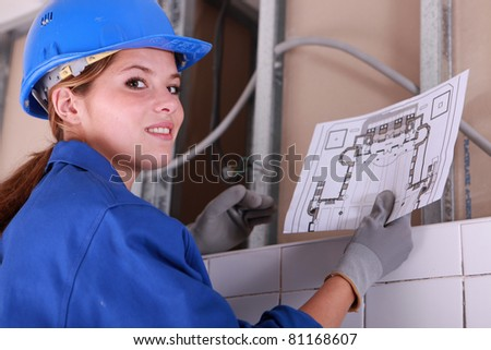 Brunette electrician holding diagram - stock photo