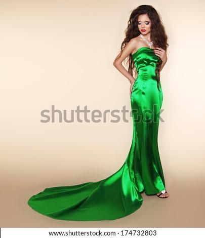Brunette elegant woman in long dress with train. Fashion model posing. Super star