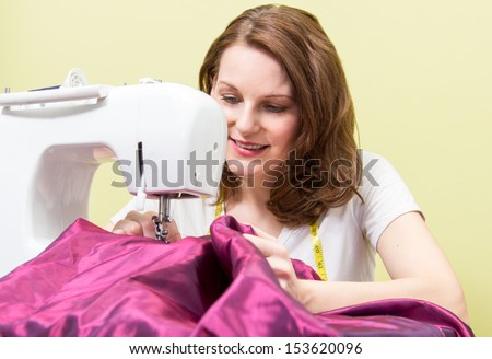 Brunette european woman sewing diy at home in front of yellow background