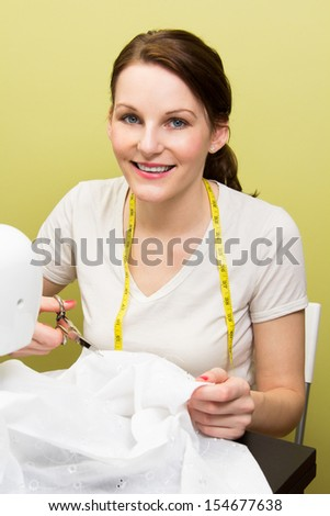 Brunette european woman sewing diy at home in front of yellow background - stock photo