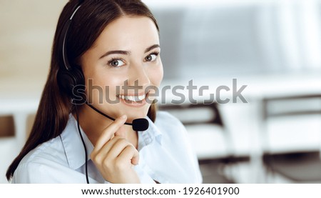 Brunette female customer service representative in a headset is consulting clients online. Call center and business people concept