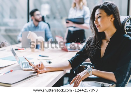 Brunette female office employee checking mail on smartphone device using 4G internet sitting at meeting table with laptop computer during brainstorming.Young woman in formal wear updating profile