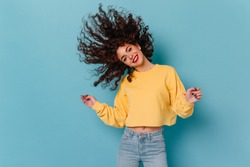 Brunette girl dances and plays wavy hair against blue background. Portrait of cute girl in yellow sweatshirt