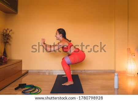Brunette girl enjoying exercising squatting working buttocks in the living room with some tapes. Beautiful caucasian girl exercising at home by the covid.