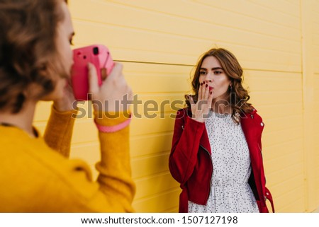 Brunette girl expressing amazement on yellow background. Woman with pink camera making pictures.