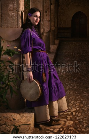 Brunette girl in a medieval suit in a Agia Napa Medieval Monastery background