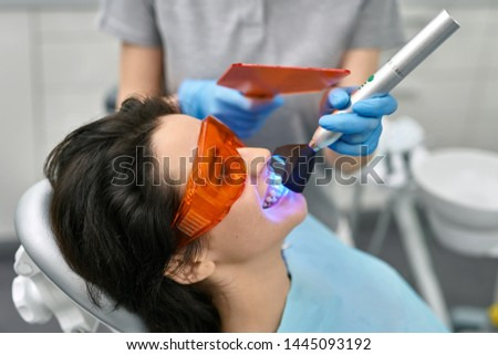 Brunette girl in a patient's bib and orange UV protective glasses in a dental clinic. Dentist in blue latex gloves is using whitening UV lamp on her teeth. Closeup horizontal photo.