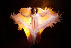 Brunette girl in an elegant dress and with white angel wings on a black background. Model, actress or dancer posing in the studio