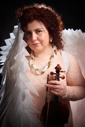 Brunette girl in an elegant dress, with violin and white angel wings on a black background. Model, violinist, actress posing in the studio