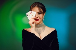 Brunette girl in black dress, necklace and earrings. Smiling, covered her eye by two aces, posing on colorful background. Poker, casino. Close-up