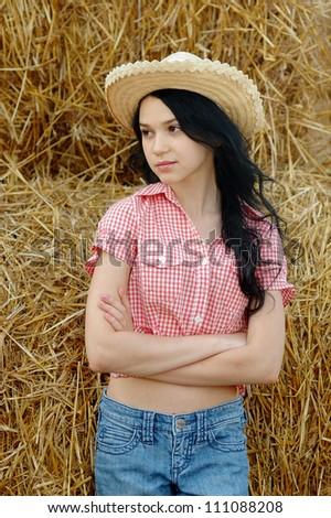 Brunette girl on fresh straw at field